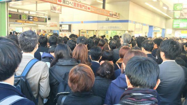 電車が止まって混雑する人々